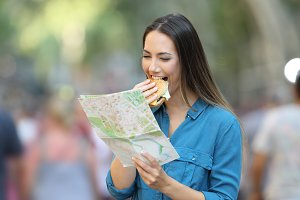 Woman eating and reading a map
