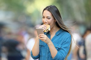 Woman eating and holding phone