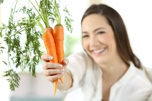 Satisfied woman showing carrots