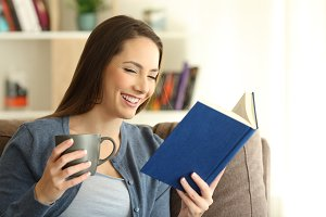 Happy woman reading a paper book