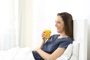 Happy woman on a bed with juice