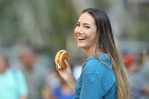 Happy woman holding a burger
