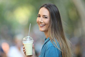 Happy lady holding a smoothie