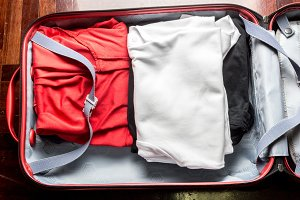 Open suitcase on a wooden  with clot