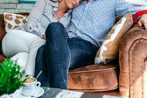 Man hugging woman on a sofa