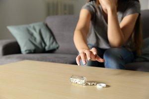 Depressed girl catching antidepressa