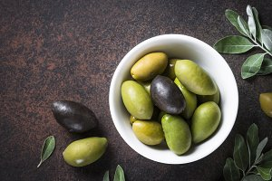 Olives and olive oil on dark stone