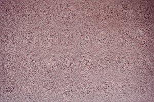 Pink bumpy stucco wall background.