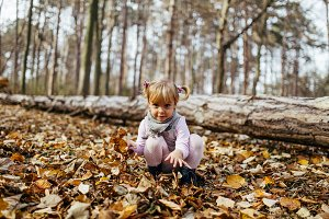 Child playing in autumn park