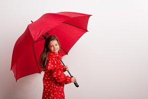 A small girl under an umbrella on a