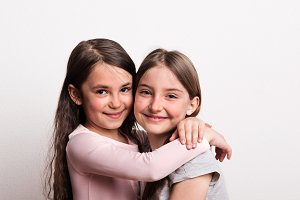 Two small girls standing in a studio