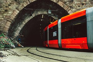 Red city tram drives from the tunnel