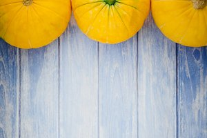 Orange pumpkins on blue wooden backg