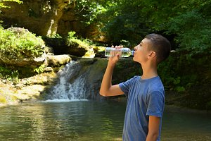 Boy drinks water from bottle outdoor