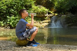 Boy drinks water sitting on stone