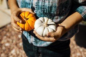 Boy Holding Pumpkins In His Hands