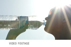Woman drinking water in sunlight