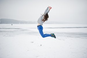 Funny jumping girl on frozen lake in