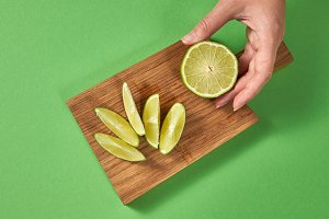Slices of lime on a board on a green