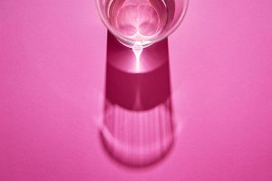 Clean glass with water on a pink