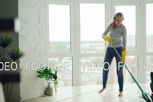 Joyful young lady is doing housework