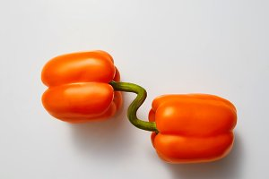 Two ripe orange peppers isolated on