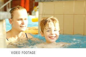 Happy boy and his mother swimming