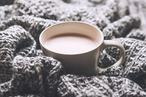 Cup of hot cocoa with milk on plaid.