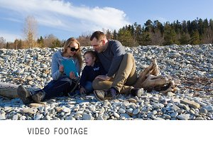 Family of three sitting on the stony