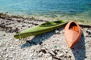 Two colour kayaks on the beach