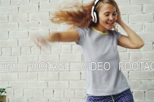 Excited young lady is dancing on bed