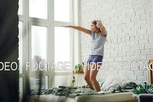Joyful young woman is dancing on bed