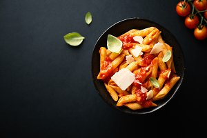 Tasty tomato pasta in bowl on dark