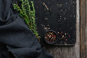 Black cutting board, spices, herbs