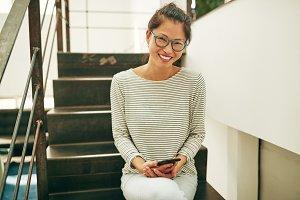 Smiling Asian businesswoman sitting
