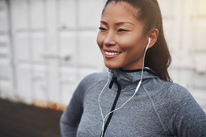 Smiling Asian woman listening to mus