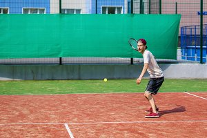 young man playing tennis on the cour