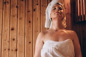 Woman sitting in a wooden spa