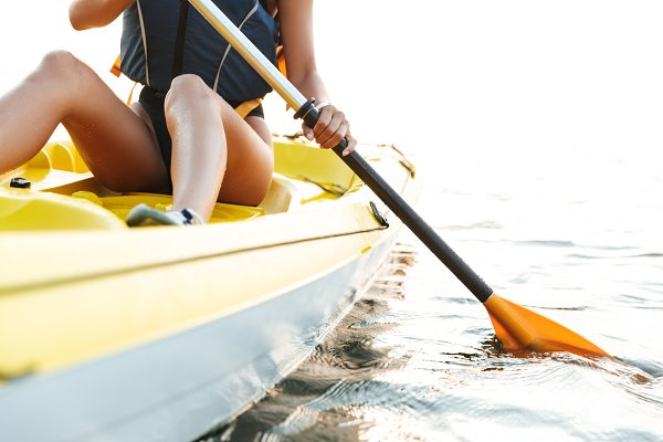 Sports Stock Photos: Royalty-free images - Young woman kayaking on lake sea in