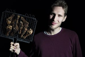 man holds cooked fried meat barbeque