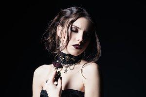 Lovely sad goth girl holds dead rose