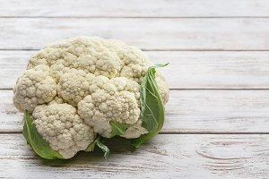 Fresh cauliflower on wooden table.