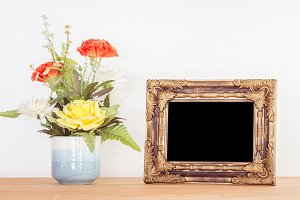 Photo frame and flowers on wooden