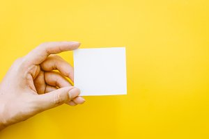Hand holding paper on yellow