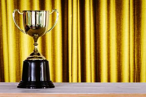 Champion golden trophy on wood table