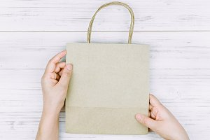Hand holding shopping bag on wooden