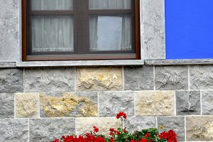 Windows with flowers in blue facade