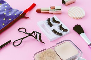 Make up bag with cosmetics on pink