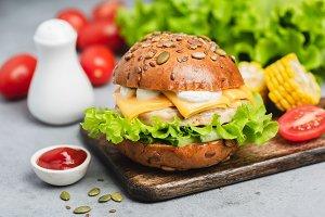 Chicken cheeseburger on wooden board