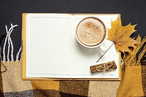 Opened notebook, cup of cocoa